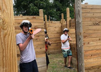 3 jeunes cachés jouant au laser game